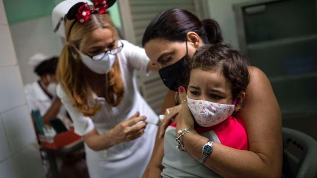 Một người mẹ bồng con gái trong buổi tiêm liều vắc-xin Soberana-02, tại một phòng khám ở Havana, Cuba, hôm 16/9