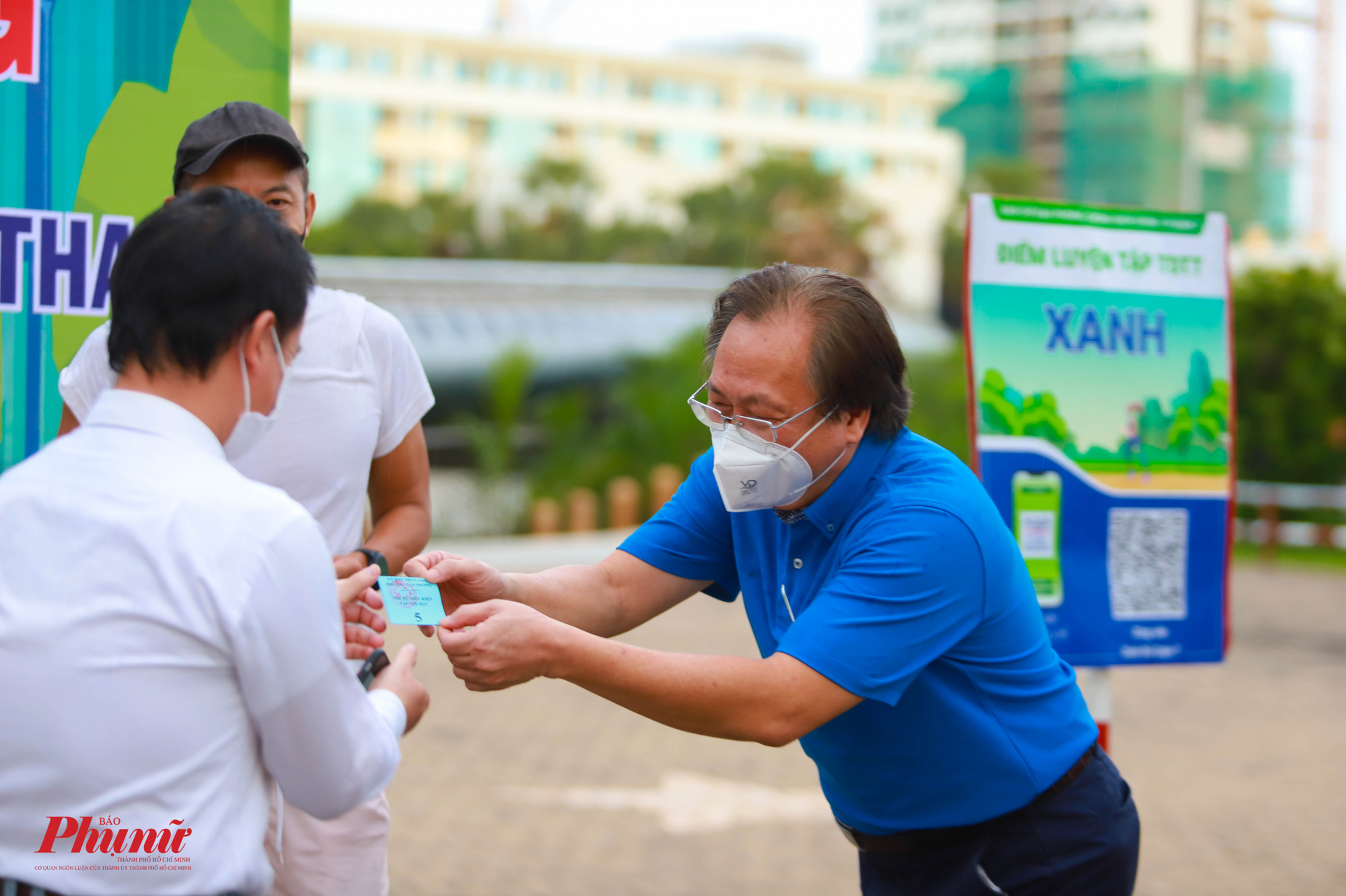 Ông Mai Bá Hùng - Phó Giám đốc Sở Văn hóa Thể thao TPHCM trao phiếu tập thể dục cho người dân đăng ký đợt đầu