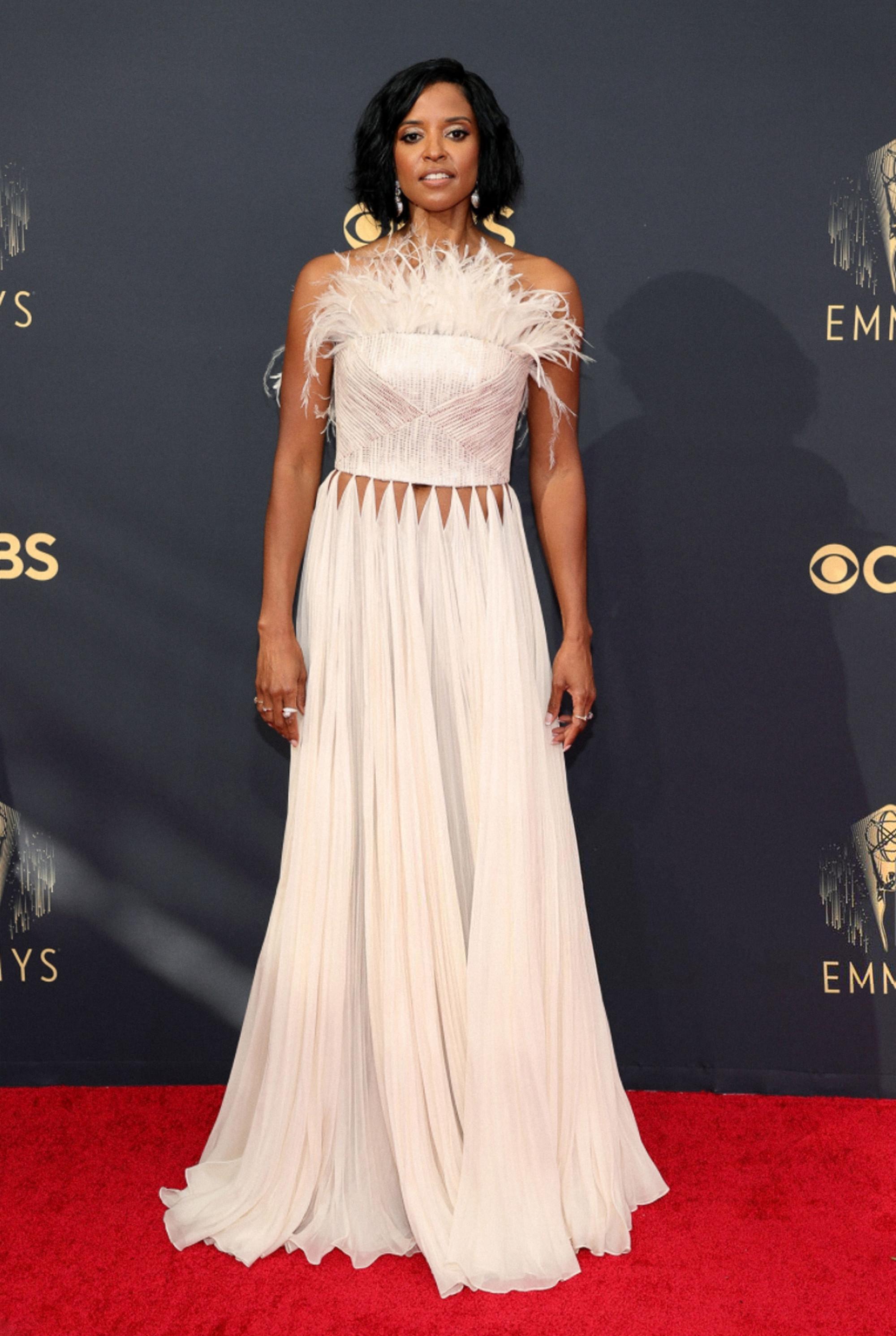 Nữ diễn viên Renee Elise Goldsberry cũng chọn trang phục của Công Trí để xuất hiện tại thảm đỏ Emmy năm nay, nhưng nằm trong BST Thu - Đông 2020. Chiếc áo cúp ngực được làm bằng vải tweed đính kết lông vũ kỳ công. Trong khi đó, phần chân váy được thực hiện bằng chất liệu tơ tằm để tăng sự quyến rũ, mềm mại.