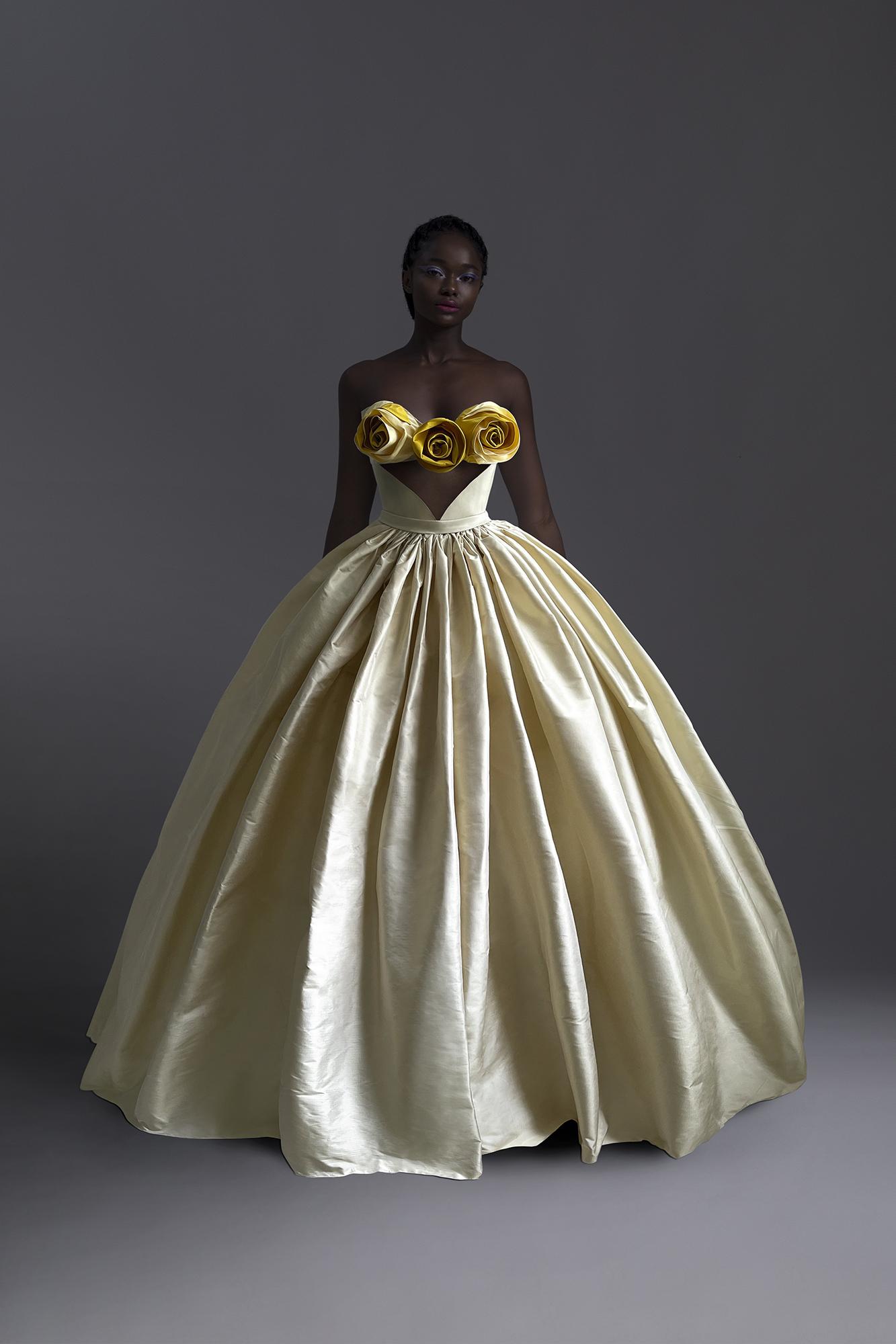 Chiếc váy xoè điệu đà trở nên ấn tượng nhờ chi tiết hoa hồng 3D ở ngực được xử lý khéo léo. BST lần này được anh thực hiện chủ yếu trên nền vải taffeta.