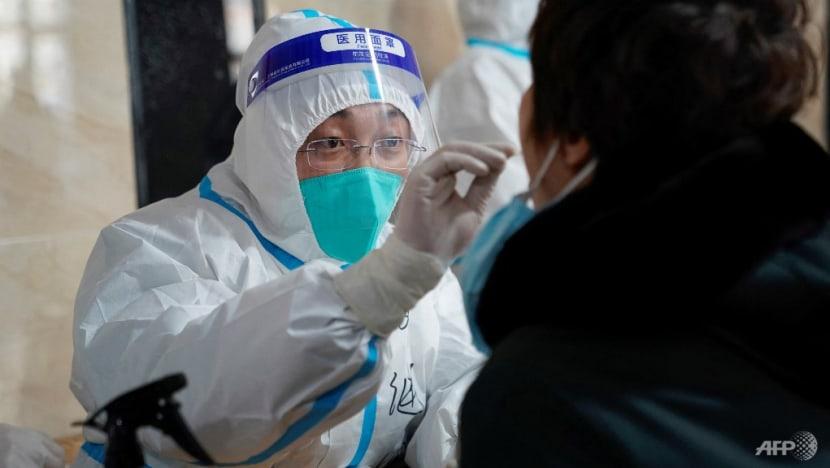 Nhân viên y tế lấy mẫu từ người đàn ông để xét nghiệm COVID-19 tại một tòa nhà văn phòng ở Cáp Nhĩ Tân