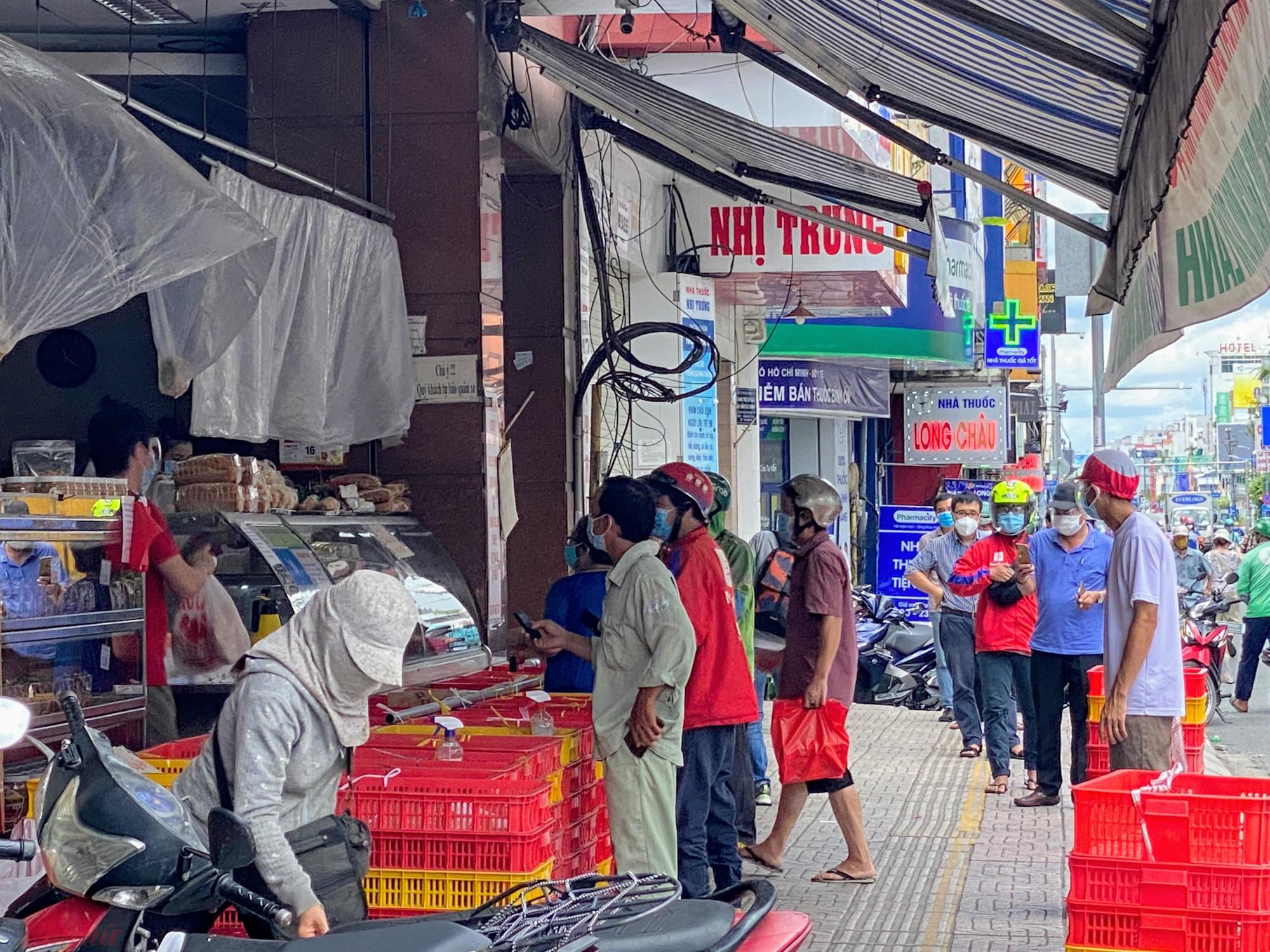 Một cửa hàng bánh ngọt trên đường Hai Bà Trung (quận 1) ông nghịt khách. ngoài shipper vẫn có khách lẻ mua bánh, do số lượng khách đến mua đông, theo quan sát của phóng viên có cả lực lượng công an khu vực đến để nhắc nhỡ, hướng dẫn khách giữ khoảng cách, xếp hàng khi mua bánh.
