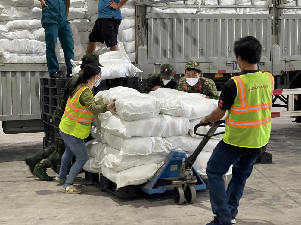 Lực lượng quân đội hỗ trợ dỡ hàng và vận chuyển đến các kho an sinh của Trung tâm An sinh TPHCM - Ảnh: Thu Duyên