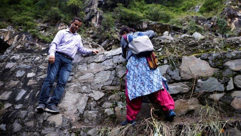 Bimla Thakur, một nhân viên y tế 56 tuổi, đã đi bộ xuyên qua các vách núi để tiêm phòng cho người dân ở các ngôi làng hẻo lánh như Malana, thuộc bang Himachal Pradesh, Ấn Độ (Ảnh: Rueters)