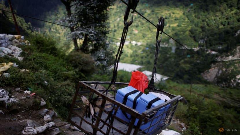 Bộ dụng cụ y tế và hộp chứa vắc xin COVISHIELD, được vận chuyển trên một chiếc lồng sắt có gắn ròng rọc, vượt qua hẻm núi để đến làng Malana (Ảnh:Reuters