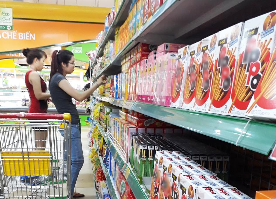 Nhiều người tiêu dùng đã có thói quen xem hàm lượng đường, chất béo… trên bao bì trước khi mua - ẢNH: H.LÀI