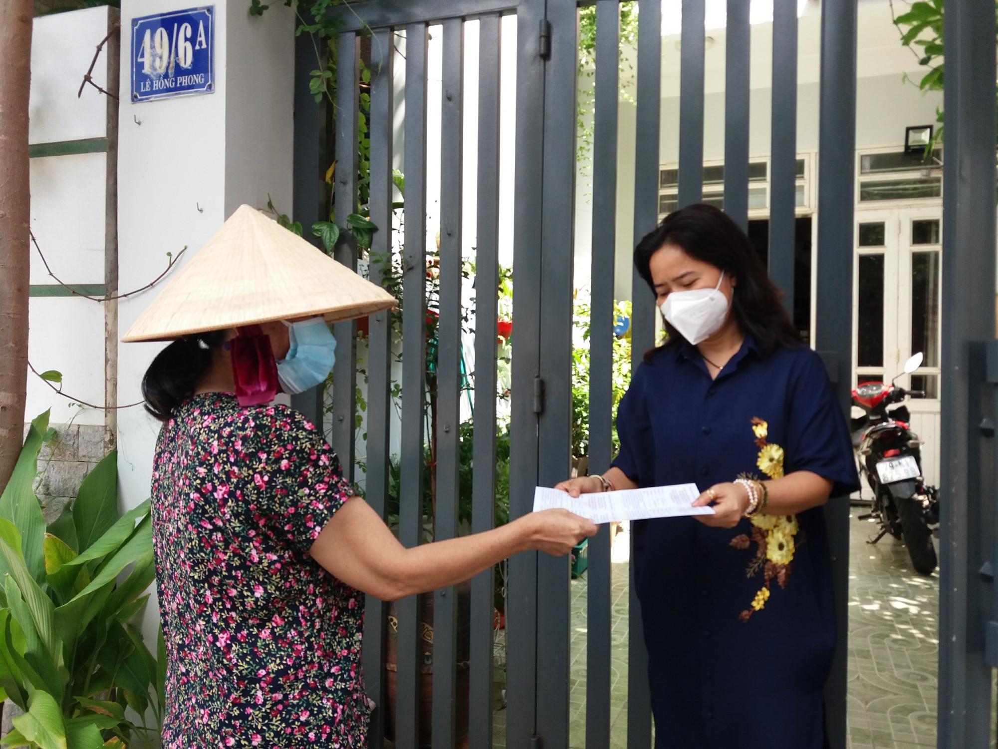 Bà Liên gõ cửa từng nhà để phát phiếu đi chợ cho người dân, đồng thời tuyên truyền người dân thực hiện các biện pháp phòng chống dịch