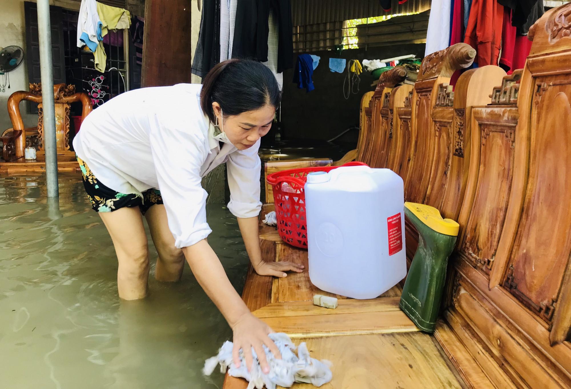 Lũ bắt đầu rút ra khỏi nhà, nhiều người dân xã Quỳnh Hồng (huyện Quỳnh Lưu) tranh thủ tận dụng dòng nước lũ để vệ sinh, lau chùi bùn đất bám trên đồ dùng.