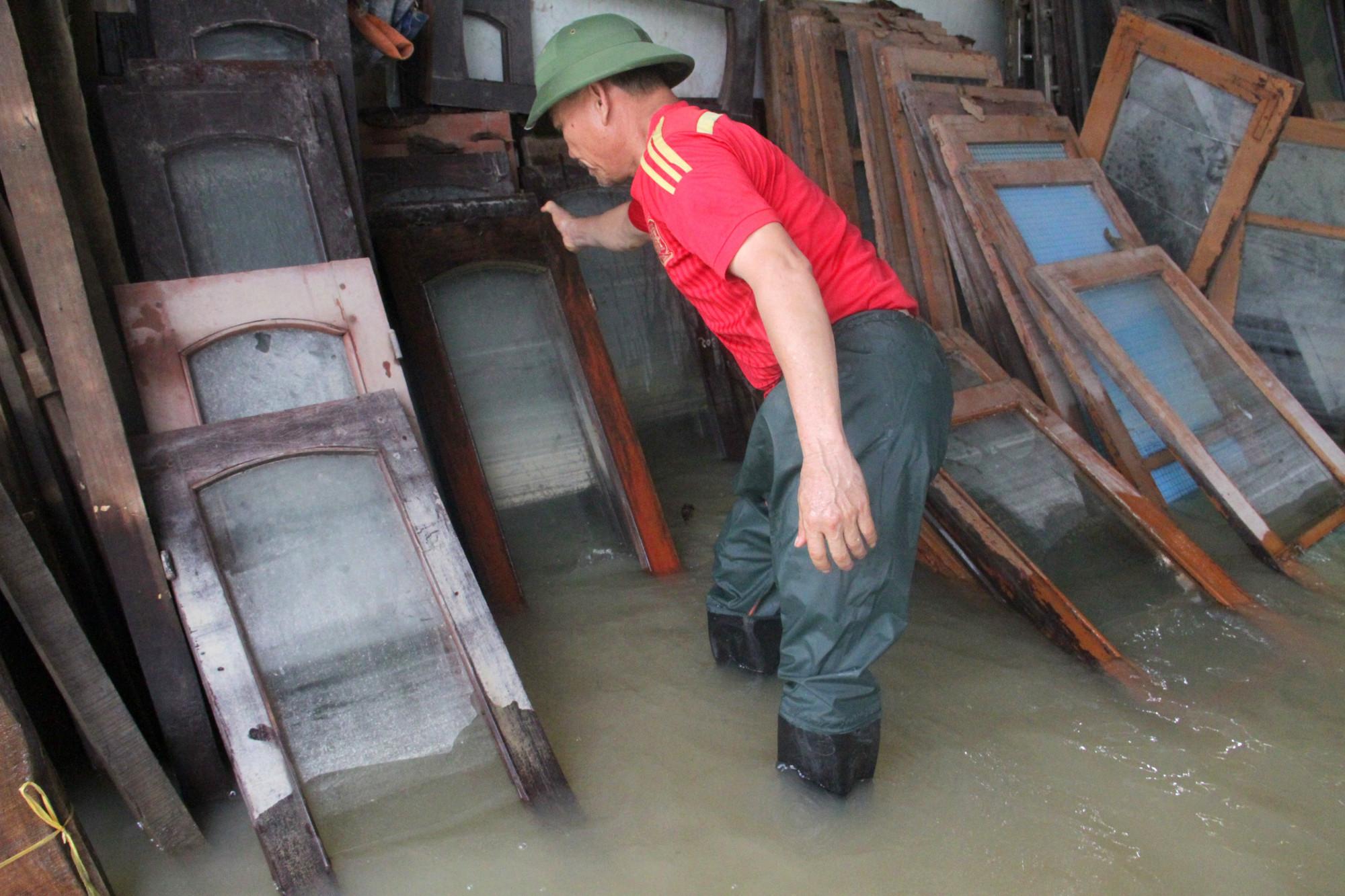 Người dân tranh thủ nước lũ rút để vệ sinh nhà cửa, lau chùi đồ đạc