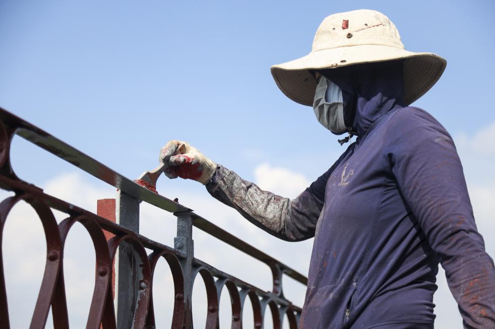 Thành cầu Long Biên chiều từ Hà Nội sanng đang được công nhân vệ sinh, sơn lót chống gỉ.