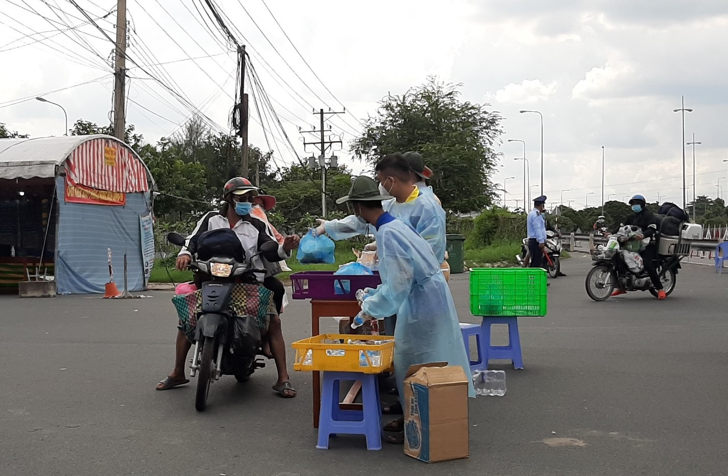 Lực lượng chức năng tại Vĩnh Long phát cơm và nước uống cho người dân tiếp tục hành trình về quê
