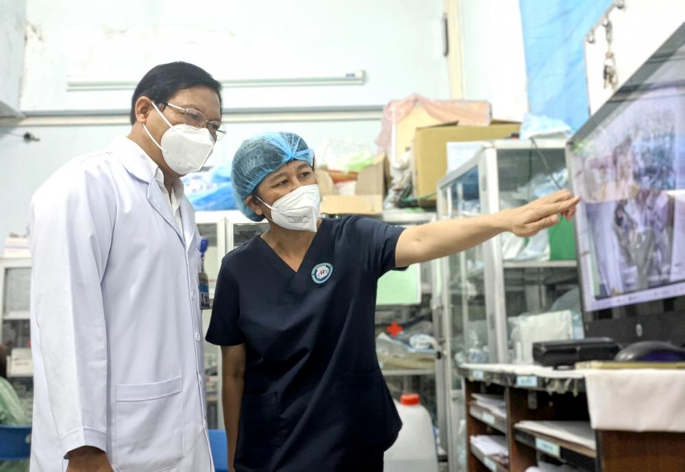 Bác sĩ Nguyễn Thanh Thúy - Trưởng khoa Hồi sức tích cực, chống độc, Bệnh viện Đa khoa khu vực Hóc Môn (phải)  - quan sát buồng bệnh từ phòng trực - ẢNH: HIẾU NGUYỄN