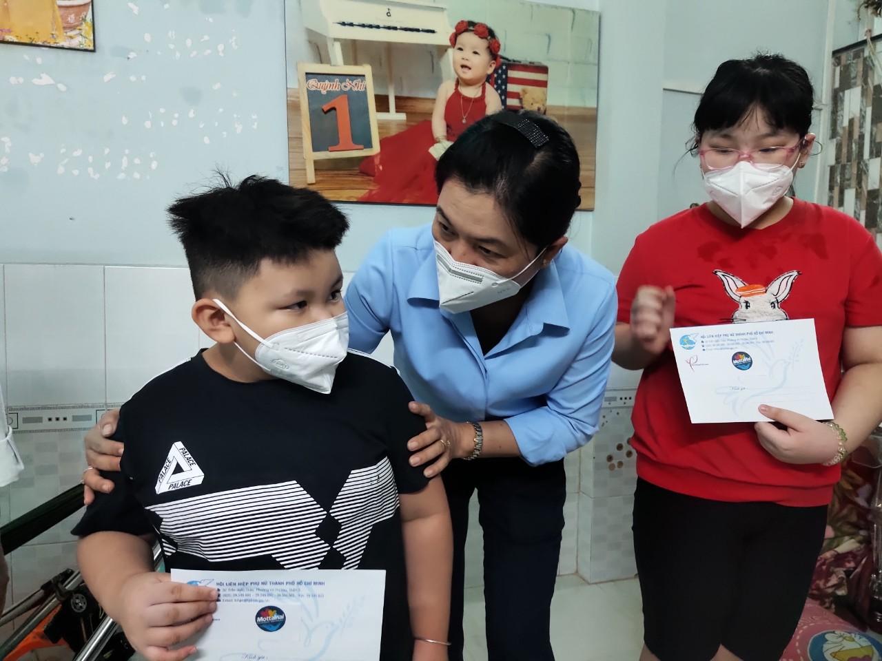 Bà Nguyễn Trần Phượng Trân - chủ tịch Hội LHPN TP - trao quà cùng số tiền 2 triệu đồng (mỗi suất) động viên hai trẻ vừa mất mẹ và bà ngoại trong đợt dịch Covid-19