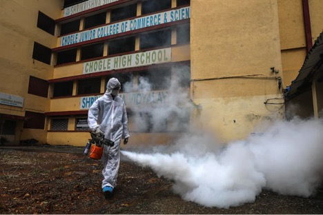 Một nhân viên y tế sử dụng máy phun khử trùng tại trường trung học Chogle ở Mumbai vào ngày 30/9, sau quyết định mở cửa trở lại lần đầu tiên kể từ tháng 3/2020 cho học sinh từ lớp 8 đến lớp 12