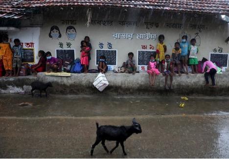 Học sinh chờ mưa tạnh để tiếp tục các lớp học ngoài trời ở Joba Attpara, Ấn Độ