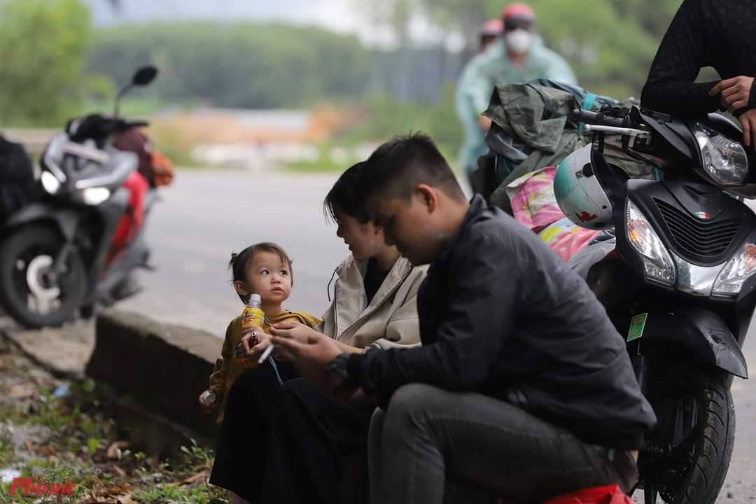 Tranh thủ lúc cơn mưa vừa tạnh đôi vợ chồng trẻ cho con nghỉ ngơi, uống nước tại khu vực gần chốt kiểm dịch số 5 ở thị trấn Lăng Cô