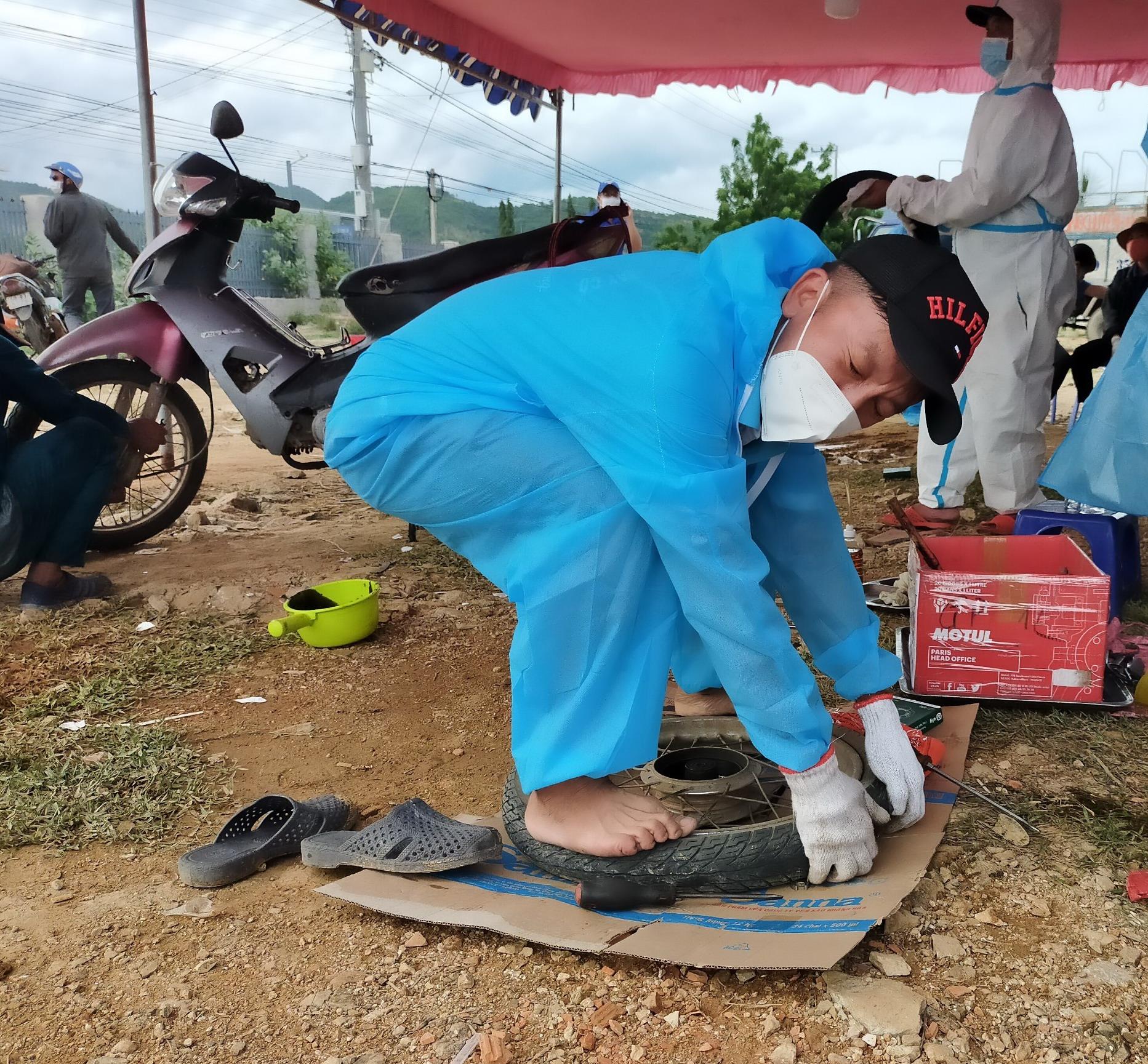 Một thợ sửa xe đang thay lốp cho xe của người dân tại trạm tiếp sức ở Cam Thịnh Đông, TP. Cam Ranh, tỉnh Khánh Hòa