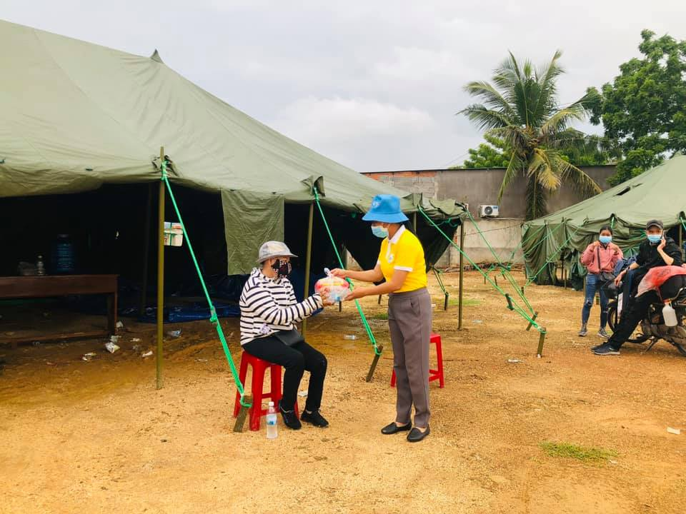 Đại diện Hội Liên hiệp Phụ nữ tỉnh Khánh Hòa trao thực phẩm hỗ trợ cho người dân về quê đang dừng nghỉ chân tại Cam Ranh