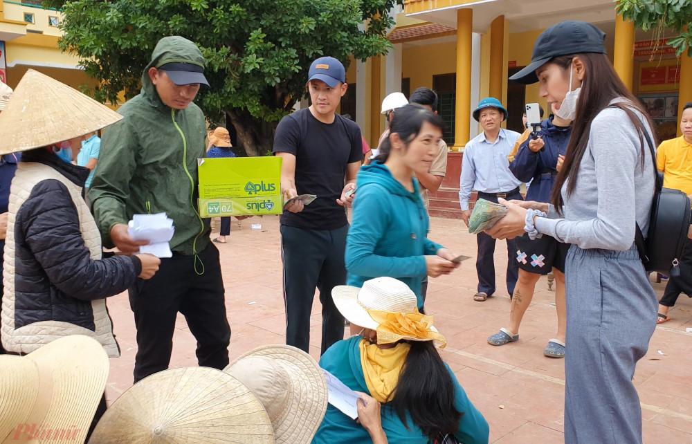 Công Vinh và Thủy Tiên trao tiền hỗ trợ cho người dân tại xã Lộc Thủy. Ảnh: Trường Nguyên