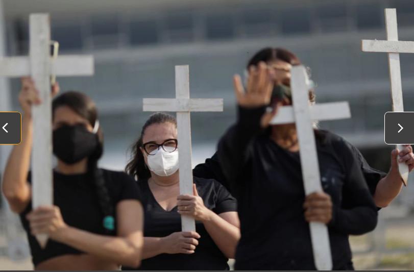 Người biểu tình phản đối Tổng thống Jair Bolsonaro cầm thánh giá tưởng nhớ hơn 600.000 người tử vong vì COVIID-19.