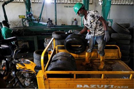 Một công nhân nhà máy Freetown dang dỡ những chiếc lốp cũ khỏi xe vận chuyển