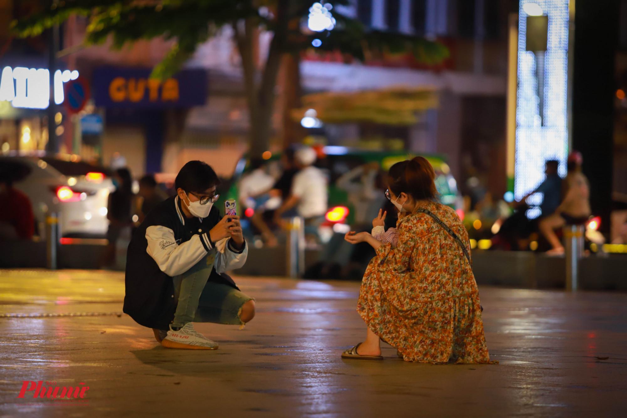 Một gia đình nhỏ chụp ảnh cho nhau tại phố đi bộ Nguyễn Huệ