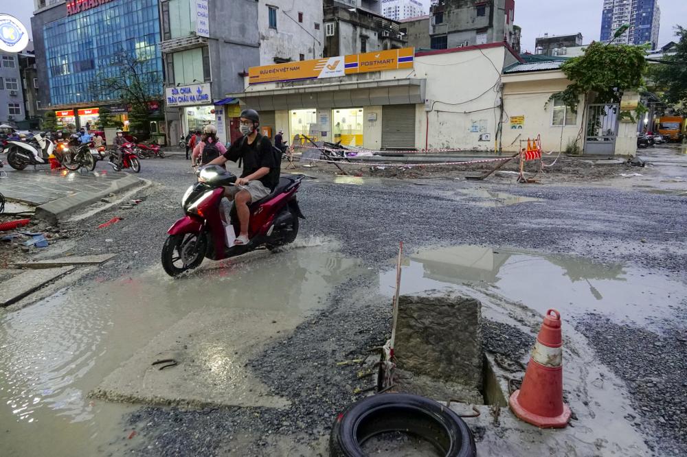 """Những """"hố tử thần"""" được che lấp bằng những vật dụng đơn sơ gây mất an toàn đối với người dân. Tình trạng mặt đường xuống cấp trầm trọng, gây ảnh hưởng nặng nề đến tình hình giao thông."""