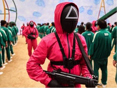 Các lính canh trong Squid game mặc trang phục khác biệt, màu hồng tươi với các hình tròn, hình vuông và hình tam giác trên mặt nạ của họ