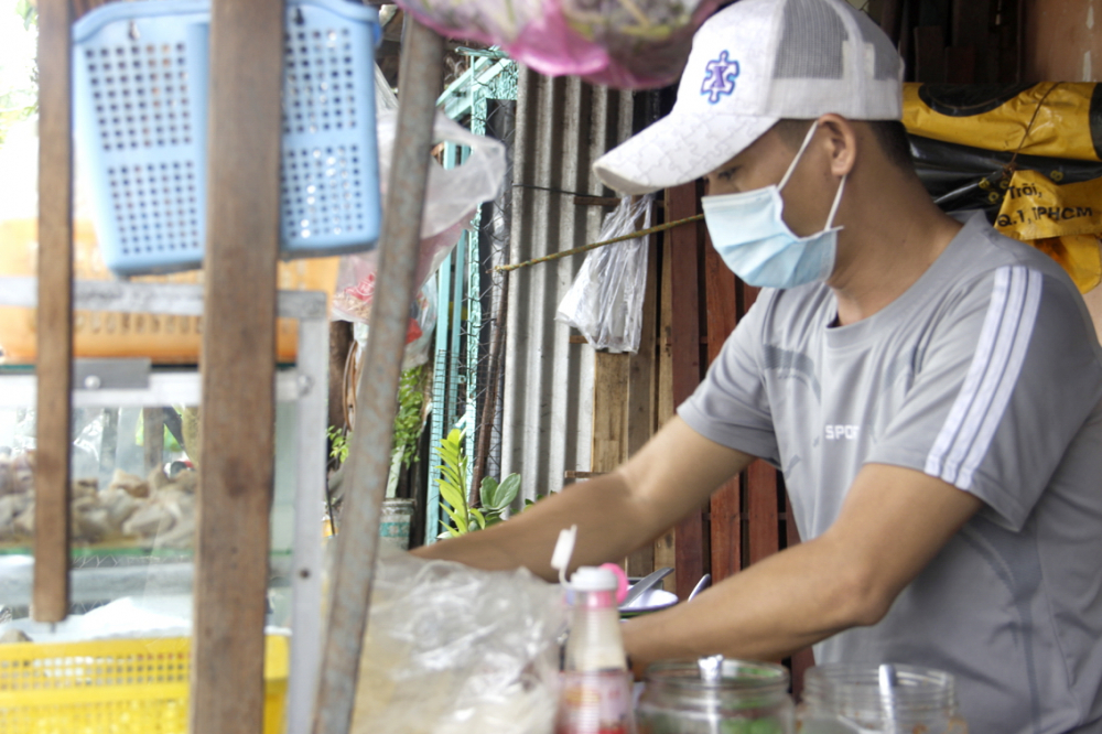 Anh Võ Minh thường xuyên đeo khẩu trang và dùng cồn khử khuẩn khi thối tiền cho khách