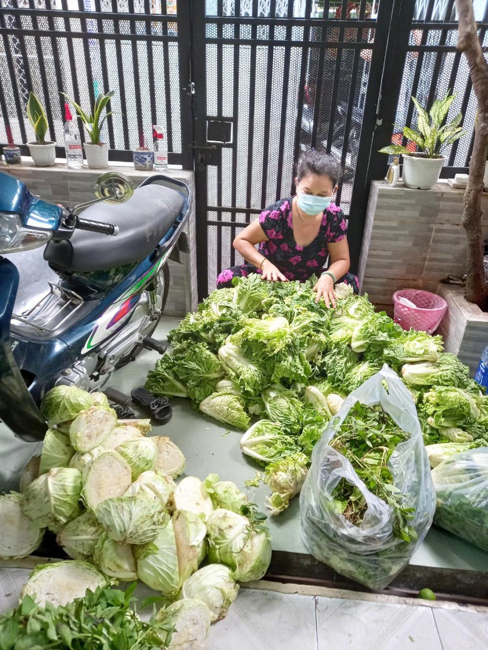 Chị Huỳnh Huệ Dung nhận rau do nhà hảo tâm đóng góp cho bếp ăn từ thiện của khu phố 6, P.5, Q.6