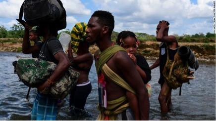 Những người di cư băng qua sông Chucunaque ở làng Bajo Chiquito, Panama, sau khi đi bộ 5 ngày qua Darien Gap.