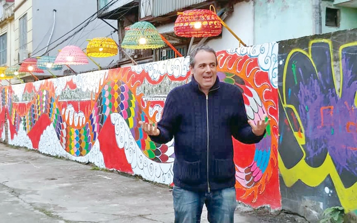NTK bên cạnh những bức tranh tường của ông và gia đình trong dự án nghệ thuật cộng đồng Phúc Tân