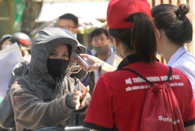 <p>Nhiều thí sinh bịt kín như ninja buộc phải tháo bỏ bớt đồ để đo thân nhiệt.</p>