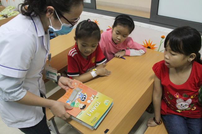 """<p style=""""text-align: justify;""""><em>Với mong muốn giúp các em không quên con chữ trong quá trình điều trị dài ngày tại trung tâm, không được đến trường, không gặp bạn bè, thầy cô và nguy cơ bỏ lỡ việc học, Trung tâm Huyết học truyền máu đã phối hợp các cô giáo trên địa bàn và một nhóm thiện nguyện mở lớp học dạy cho các bé ngay tại khoa vào mỗi tối.</em></p>"""