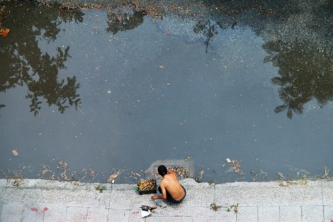 Người đàn ông lặng lẽ dọn rác sau cơn mưa