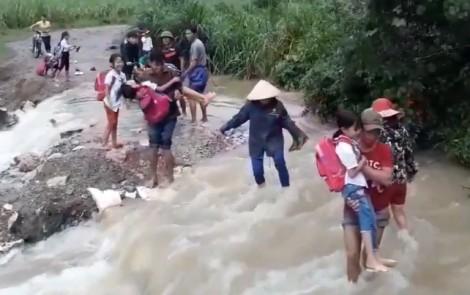 Cầu bị cuốn trôi trong bão, học sinh được cõng vượt nước siết đến trường