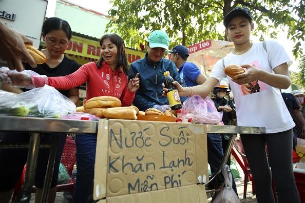 Banh mi, nuoc suoi mat lanh mien phi cho khach hanh huong le hoi Chua Ba