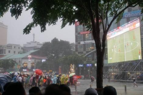 Cổ động viên đội mưa trên đường đi bộ Nguyễn Huệ cổ vũ Olympic Việt Nam