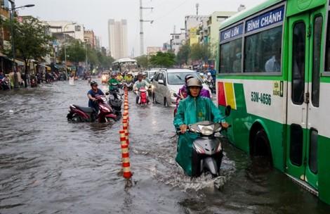 Mưa như trút nước, người dân lên cầu vượt tránh 'rốn lũ' của Sài Gòn