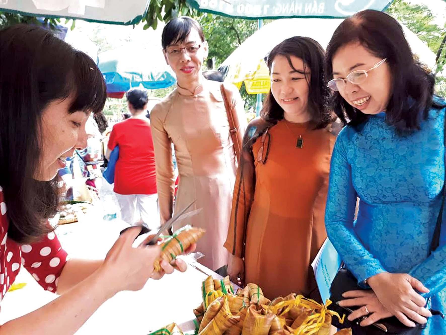 Bà Đỗ Thị Chánh - Phó chủ tịch Hội LHPN TP.HCM - tham quan các gian hàng bánh lá dừa của hội viên phụ nữ Q.6 tại hội chợ triển lãm mừng ngày thành lập Hội LHPN Việt Nam