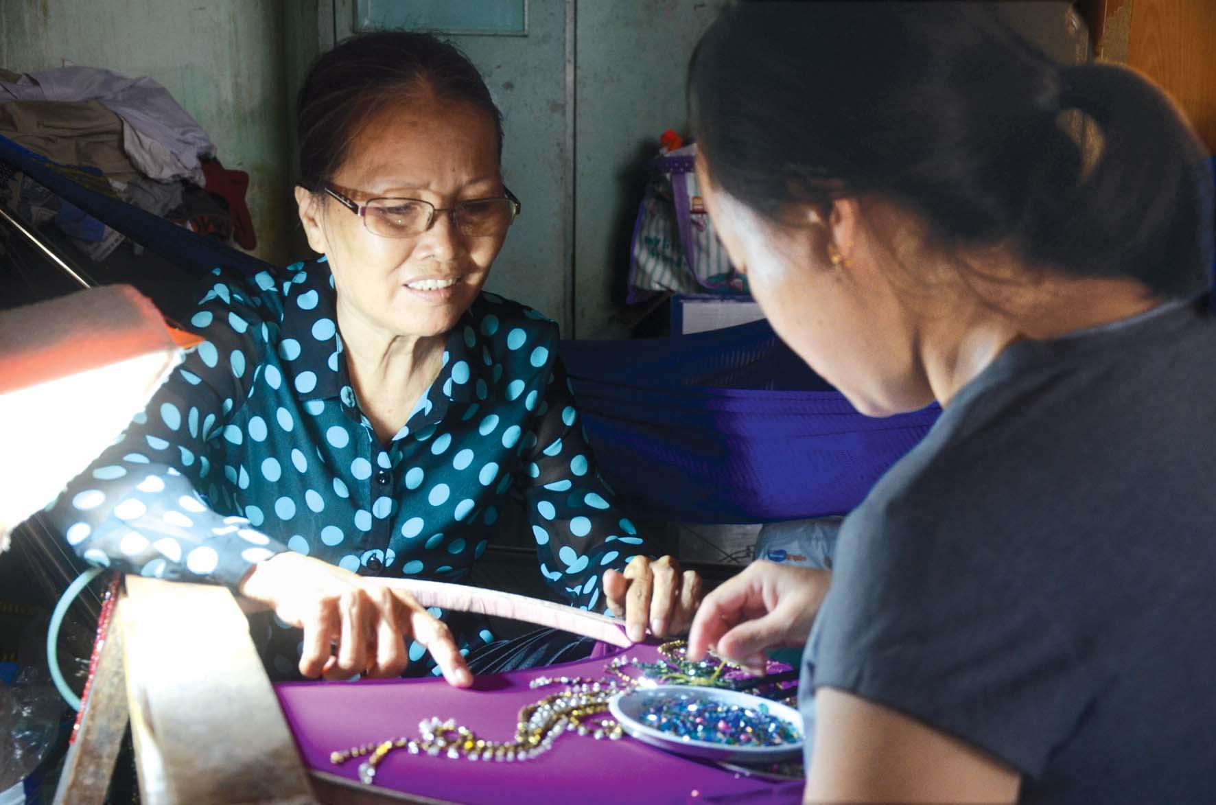 Nạn nhân nữ bị bạo hành (bìa phải) được chị Bích Thủy hướng dẫn nghề kết cườm trong thời gian tạm lánh tại địa chỉ  tin cậy cộng đồng