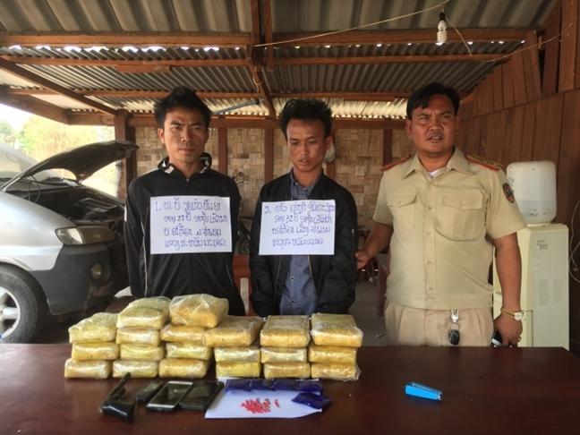 Bat 2 doi tuong nguoi Lao mang sung va 118.000 vien ma tuy dam thang vao xe bien phong