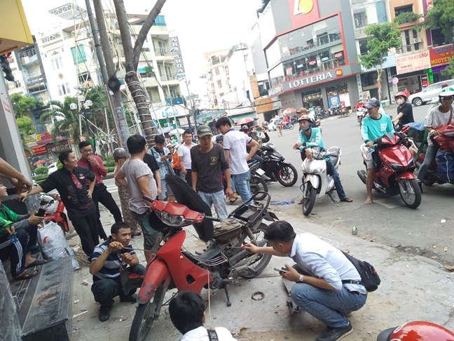 Ran chui vao xe may dung tren via he Sai Gon