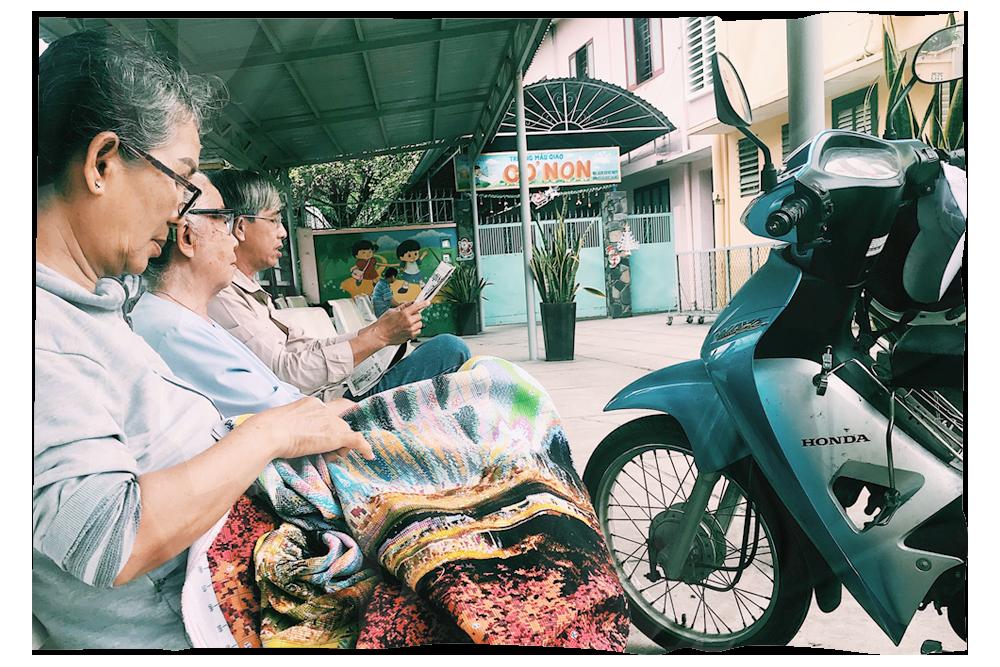 Dì Út (giữa) đang thảnh thơi ngồi nghe một giáo dân đọc báo (Ảnh: Minh Trâm)