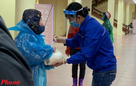 """Người lao động nghèo đội mưa đến nhận gạo tại cây """"ATM gạo"""" thứ hai của Hà Nội"""