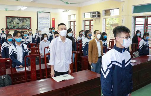 Học sinh chào cờ trong lớp ngày đầu đi học lại