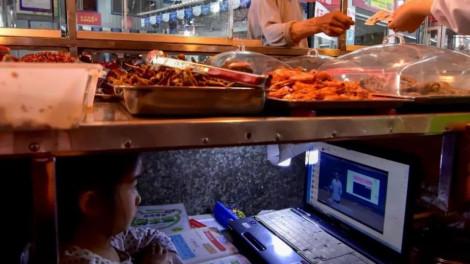 Bé lớp Một học trực tuyến dưới sạp hàng thức ăn của mẹ