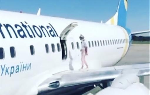 Nữ hành khách mở cửa thoát hiểm, đi dạo trên cánh máy bay vì… nóng