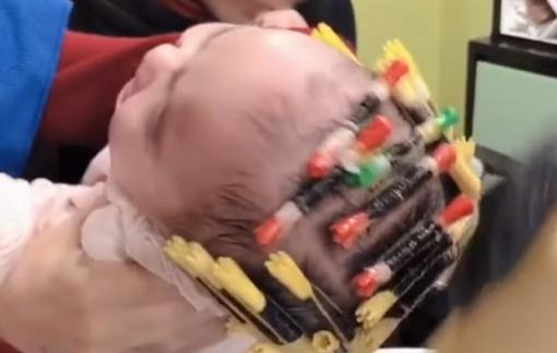 """Bé gái 1 tuổi bị """"đè ngửa"""" để uốn tóc giữa tiết trời lạnh giá"""